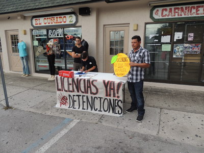 Activists with Raices en Tampa distribute information and collect petition signatures in front of a Spanish market on Fletcher Ave. - Credit: Janelle Irwin