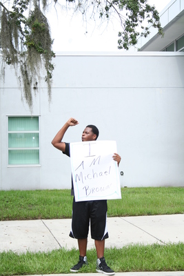 One of several local activists stands and protests Ferguson, Missouri's shooting of Michael Brown. - Credit: Crystal Farina