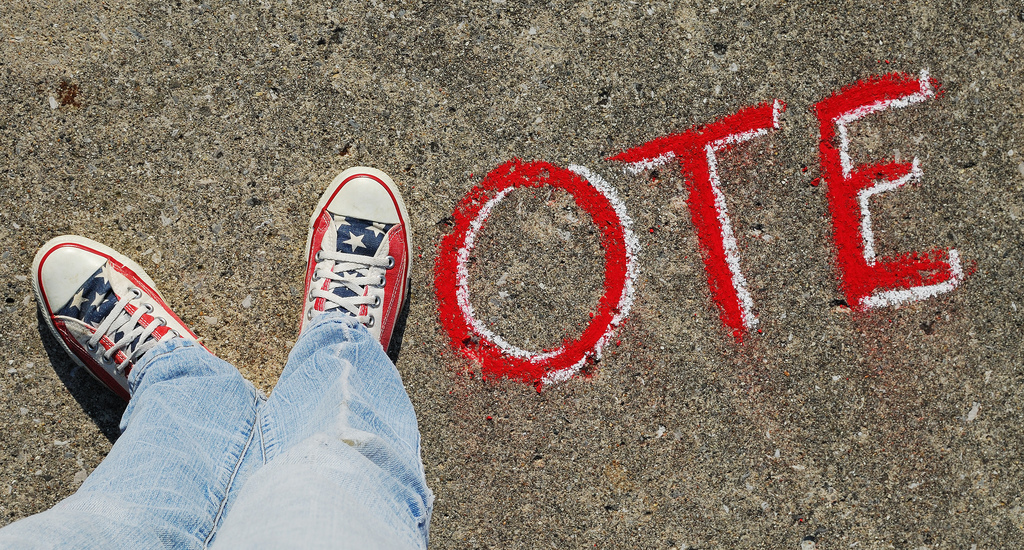 Picture of a person's feet in the shape of the letter V, followed by O T E to spell vote.