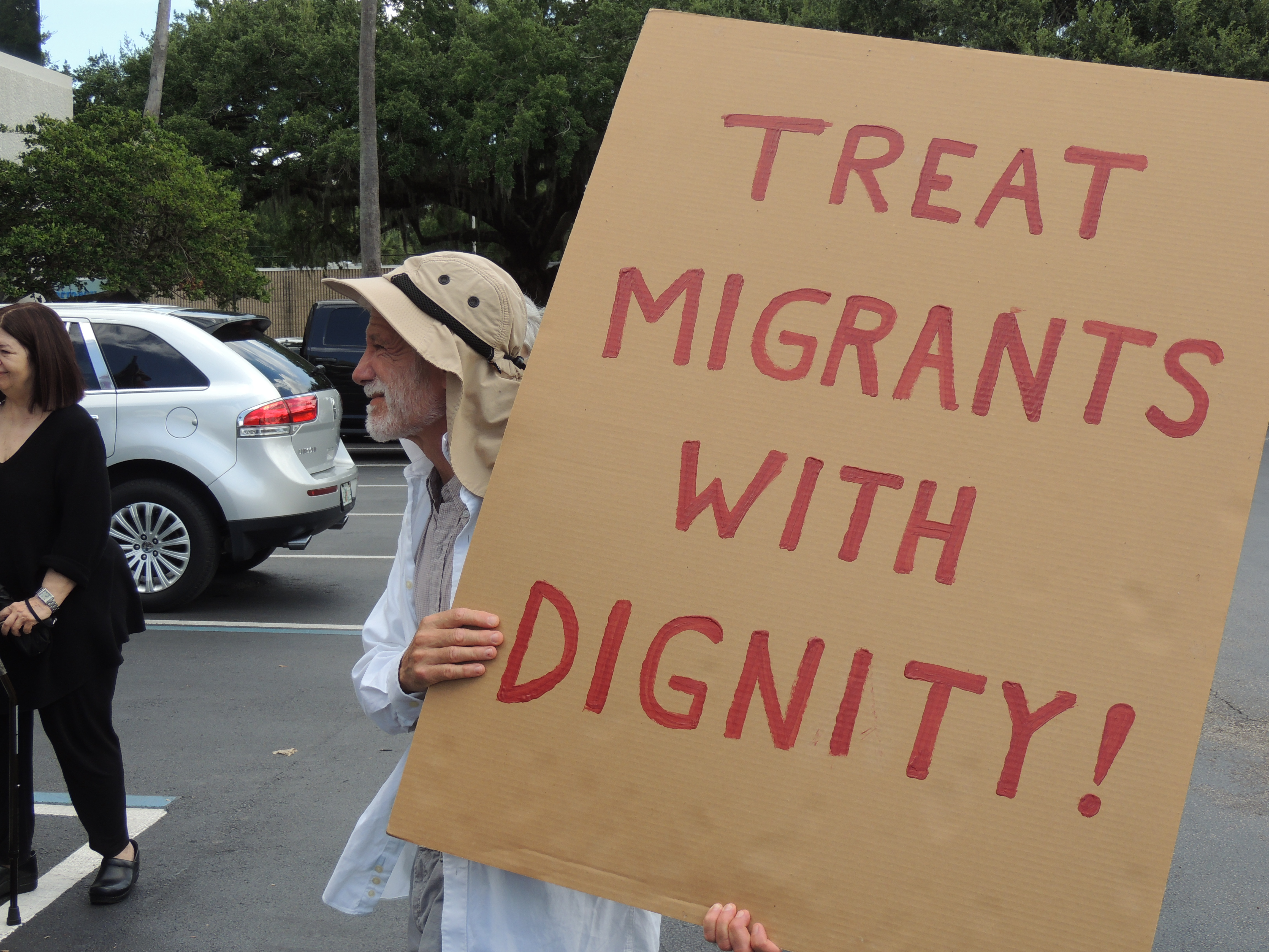 Treat migrants with dignity sign; immigration, migrant detention centers