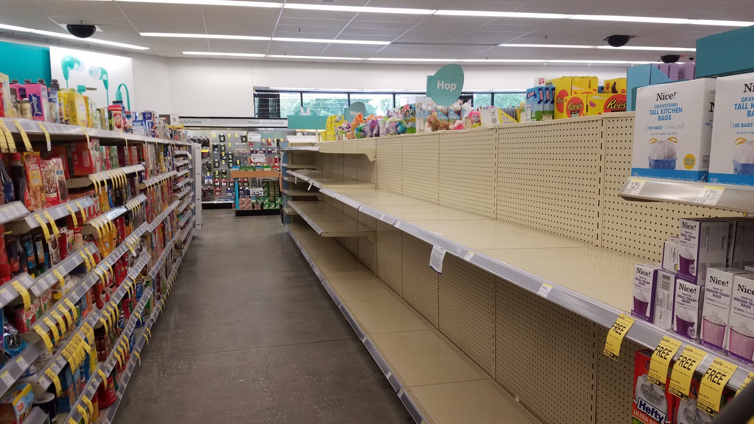 Empty store shelves with no toilet paper or paper towels because of hoarding during coronavirus emergency